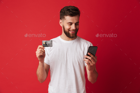 Happy young man holding mobile phone and credit card. Looking aside. - Stock Photo - Images