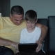 Father and Son Are Sitting on the Sofa Playing on a Tablet - VideoHive Item for Sale