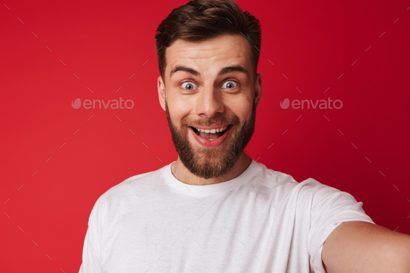 Emotional excited young handsome man make a selfie looking camera. - Stock Photo - Images
