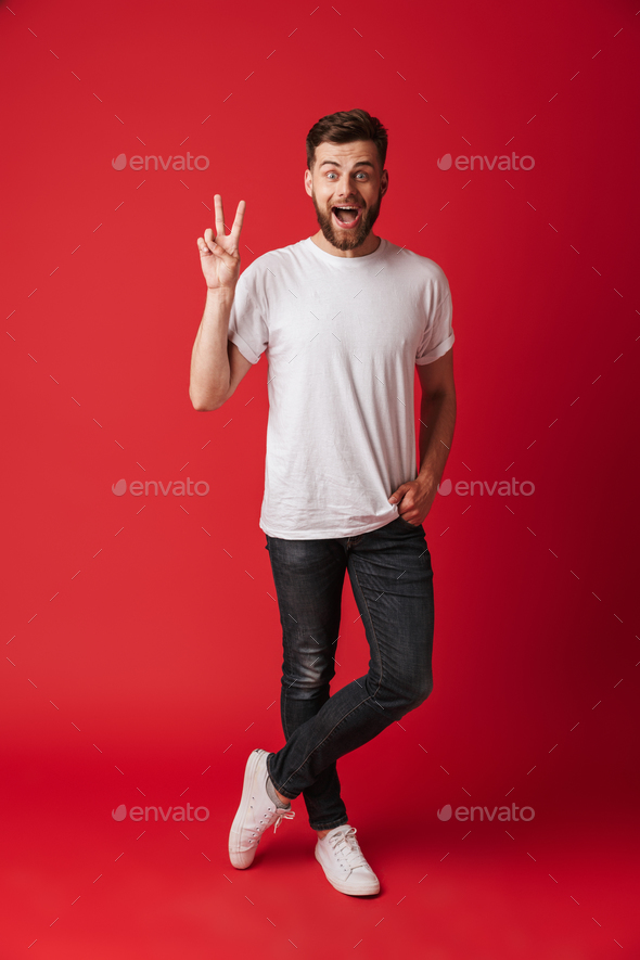 Happy young man standing isolated showing peace gesture. - Stock Photo - Images