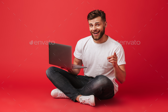 Image of handsome guy in t-shirt and jeans sitting on floor with - Stock Photo - Images