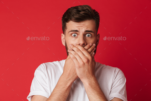 Scared young man covering mouth with hands - Stock Photo - Images
