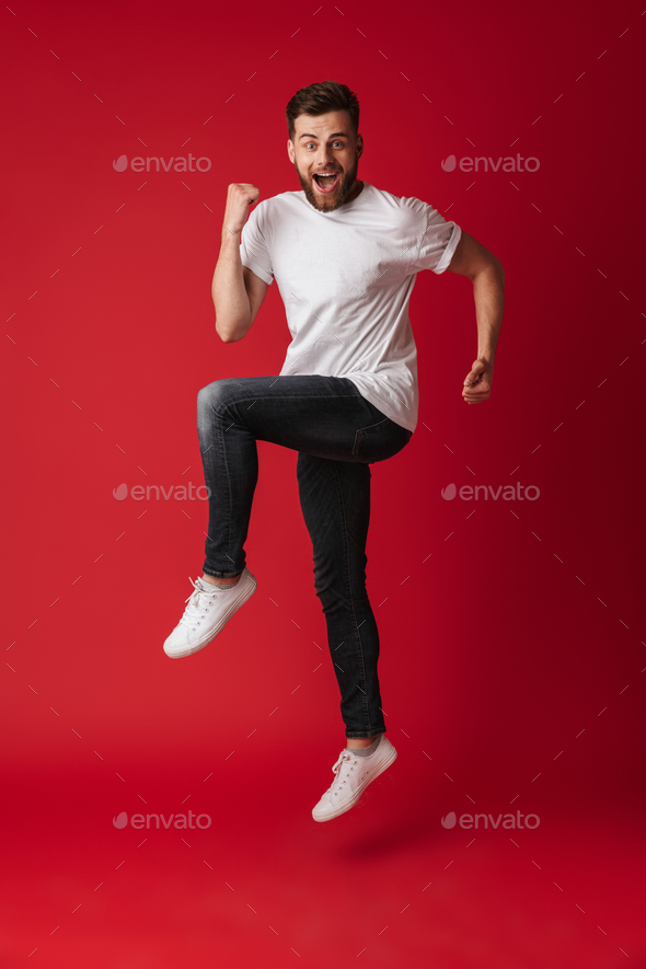 Handsome young man jumping showing winner gesture. - Stock Photo - Images