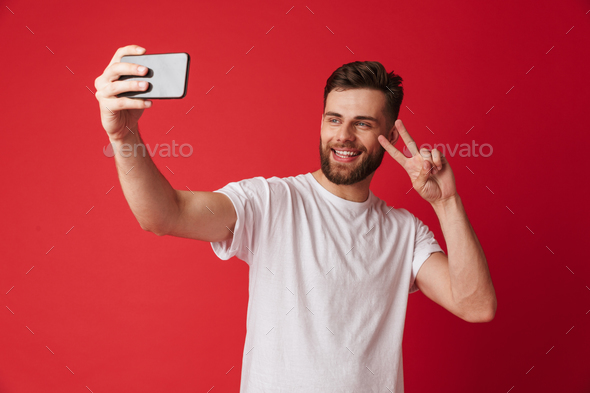 Young man standing isolated make selfie by mobile phone make peace gesture. - Stock Photo - Images