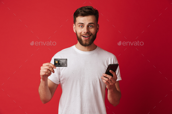 Happy young man holding mobile phone and credit card. Looking camera. - Stock Photo - Images