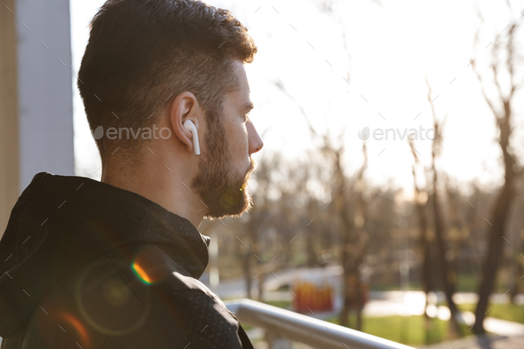 Close up of a focused young sportsman in earphones - Stock Photo - Images