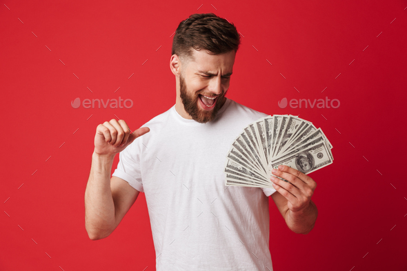 Excited young man holding money pointing. - Stock Photo - Images