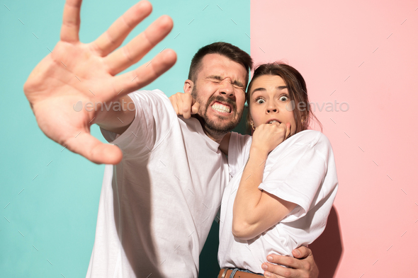 Portrait of the scared man and woman on pink and blue - Stock Photo - Images