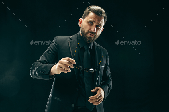 The barded man in a suit at black studio - Stock Photo - Images