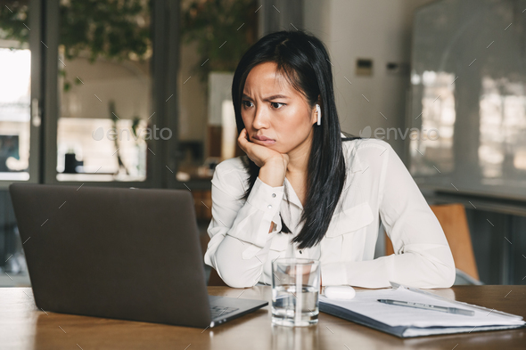 Photo of perplexed asian woman 20s wearing white shirt and bluet - Stock Photo - Images