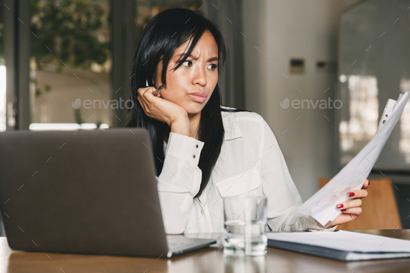 Photo of concentrated asian woman 20s wearing office clothing ho - Stock Photo - Images