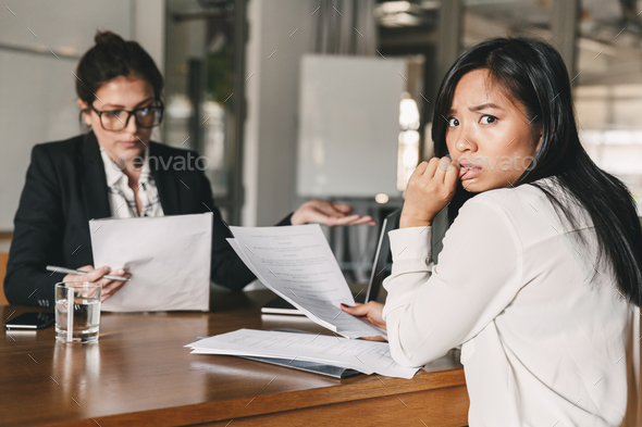 Photo of stressed asian woman expressing panic while sitting at - Stock Photo - Images