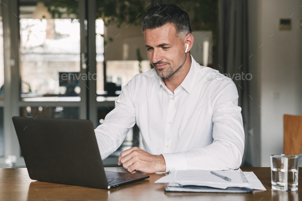 Image of handsome business man 30s wearing white shirt sitting a - Stock Photo - Images