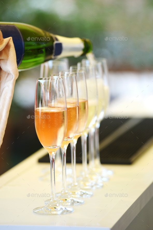 Pouring prosecco into glasses in close up - Stock Photo - Images