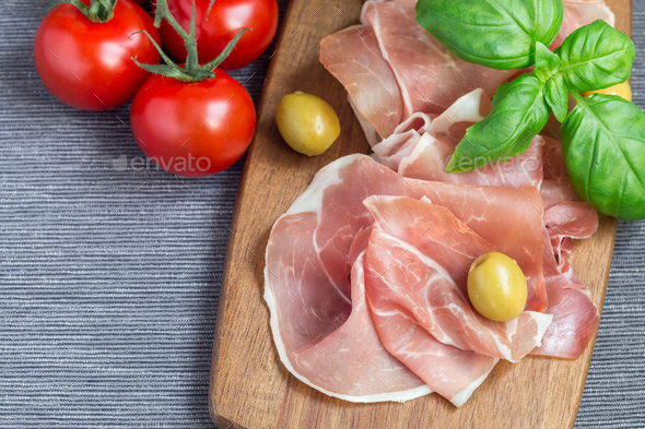 Prosciutto ham on wooden board with green olives, tomato and bas - Stock Photo - Images