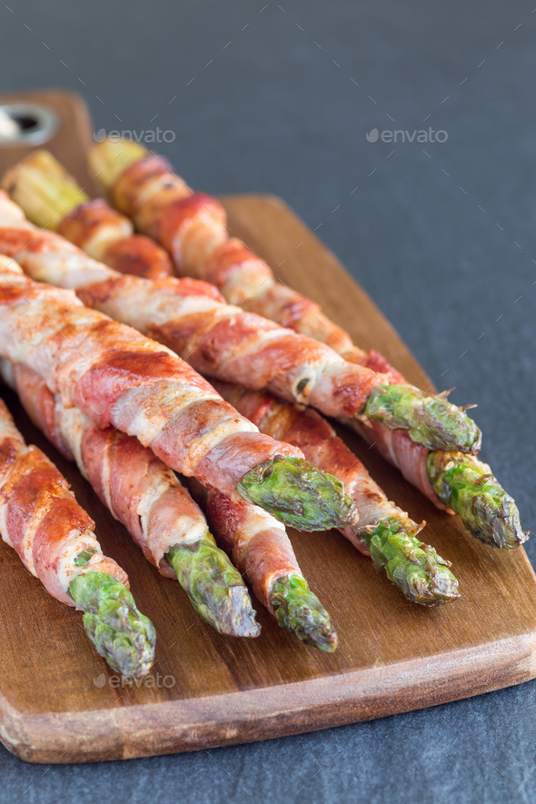Green asparagus wrapped with bacon on wooden board, vertical, co - Stock Photo - Images