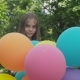 Happy Young Girl Rejoicing and Spinning with Colourful Balloons in a Park - VideoHive Item for Sale