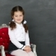 Little Girl Sitting in a Chair Near a School Board - VideoHive Item for Sale