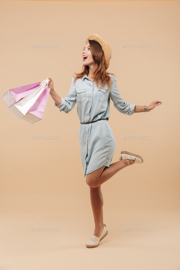 Beautiful young happy woman holding shopping bags - Stock Photo - Images