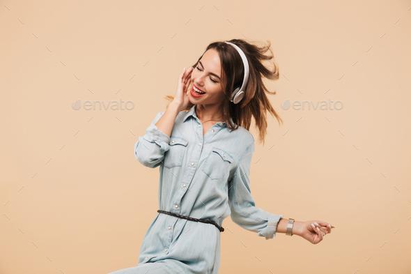 Happy woman in headphones listening music - Stock Photo - Images