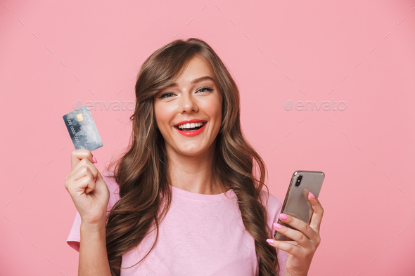 Portrait of a smiling young girl showing credit card - Stock Photo - Images