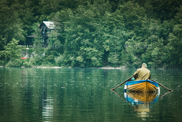 retired old man fishing from boat at lake - Stock Photo - Images