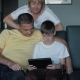 Father, Mother and Son Are Sitting on the Sofa Watching Movies and Playing Games on the Tablet - VideoHive Item for Sale
