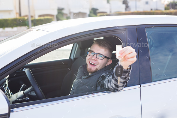 Young man hold key in white car - Stock Photo - Images