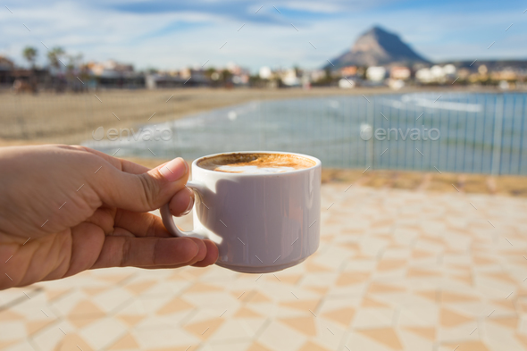 Cup of coffee in hand on the background of a beautiful beach. - Stock Photo - Images