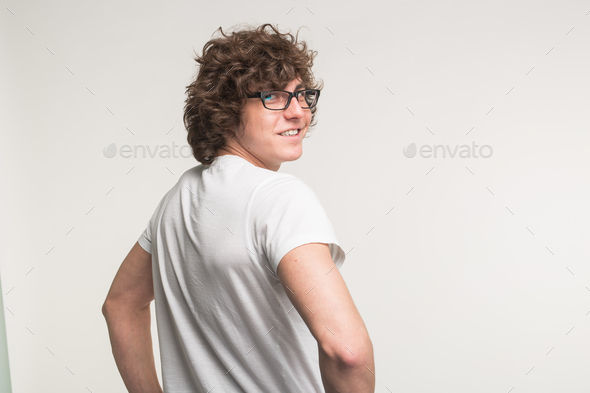 Young man in white t-shirt and glasses turning back at the camera in studio. - Stock Photo - Images