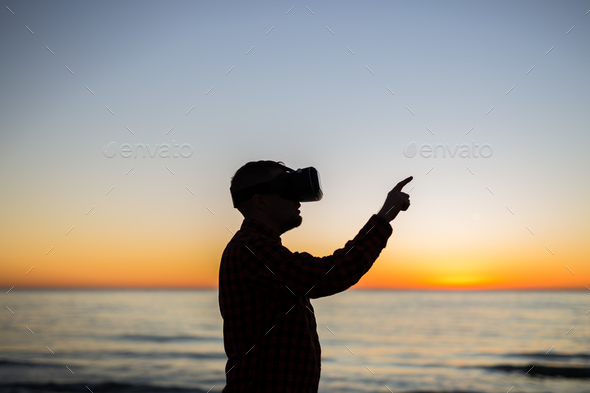 Future has come. Man wearing virtual reality goggles - Stock Photo - Images