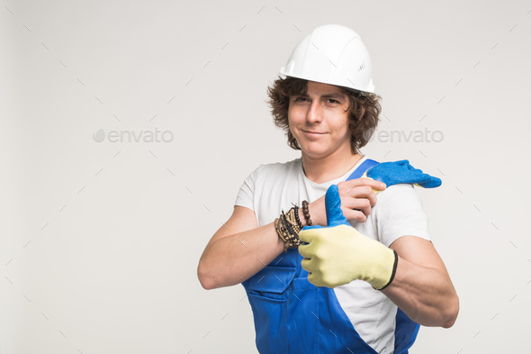 Portrait of a builder in white helmet and blue overalls with thumbs up. - Stock Photo - Images
