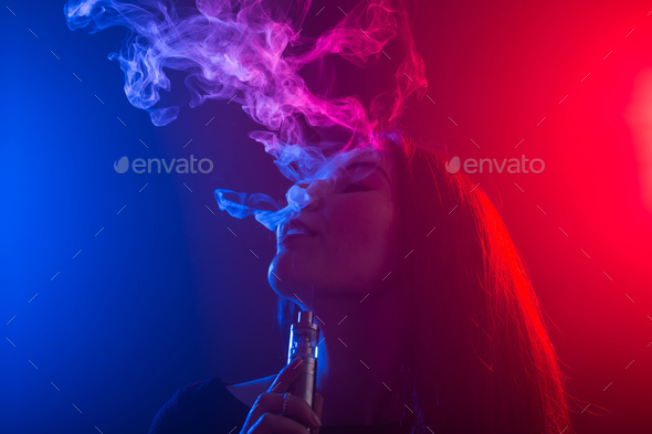 Close up portrait of vaping girl in neon blue and red light. - Stock Photo - Images