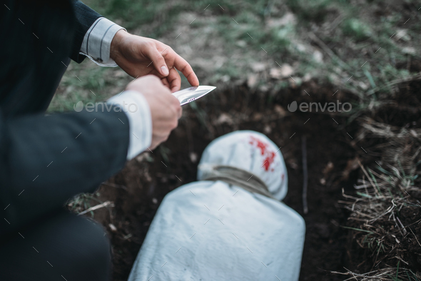 Slayer against grave, victim wrapped in a canvas - Stock Photo - Images