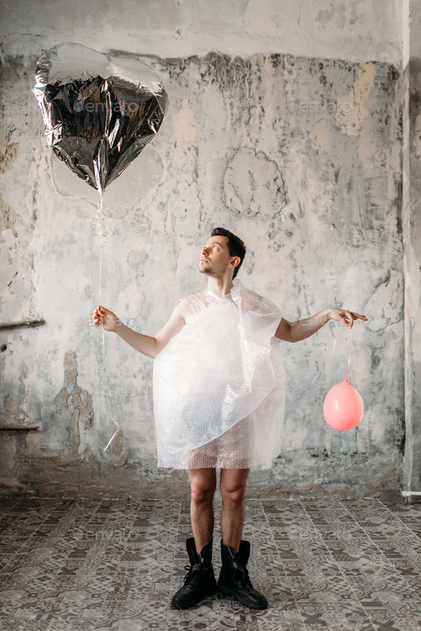 Freak wrapped in packaging film holds air balloons - Stock Photo - Images