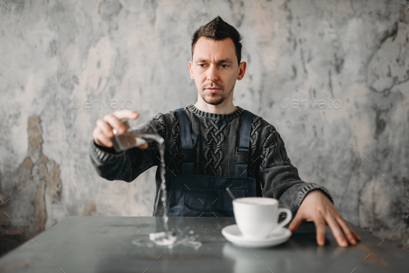 Autistic man pours water from the glass on table - Stock Photo - Images