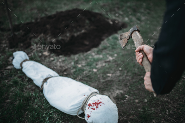 Maniac with an axe, victim wrapped in a canvas - Stock Photo - Images