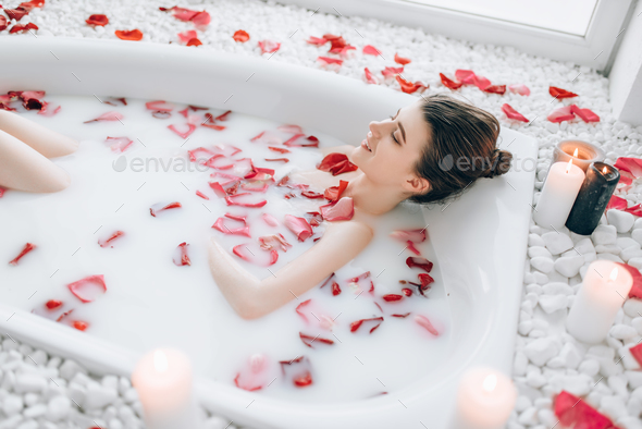 Woman sleeps in the bath with foam, rose petals - Stock Photo - Images