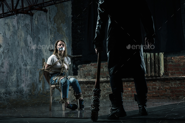 Serial maniac prepares to kill his female victim - Stock Photo - Images