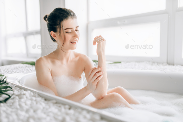 Sexy woman rubs the body with foam in the bath - Stock Photo - Images