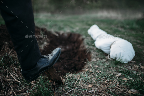 Male murderer with a shovel  is digging a grave - Stock Photo - Images