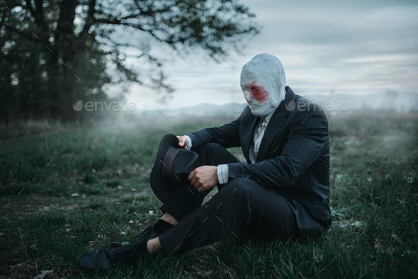 Serial maniac sitting on the ground in forest - Stock Photo - Images