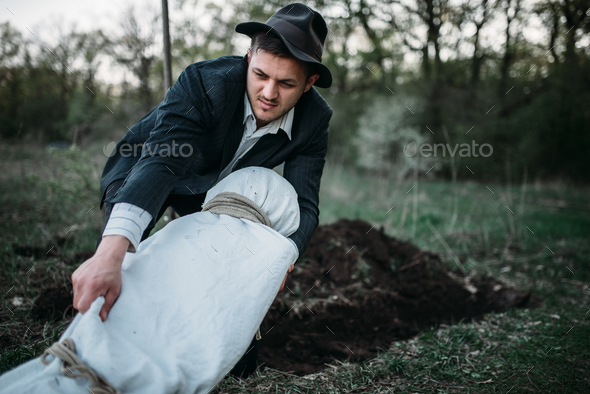 Maniac with victim's body wrapped in a canvas - Stock Photo - Images