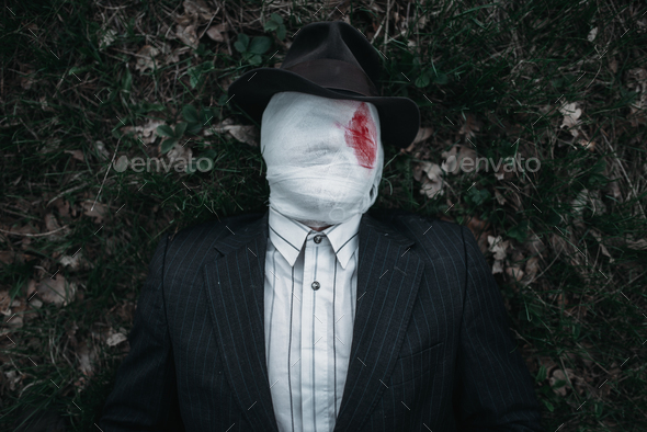 Serial maniac lies on the ground in forest - Stock Photo - Images