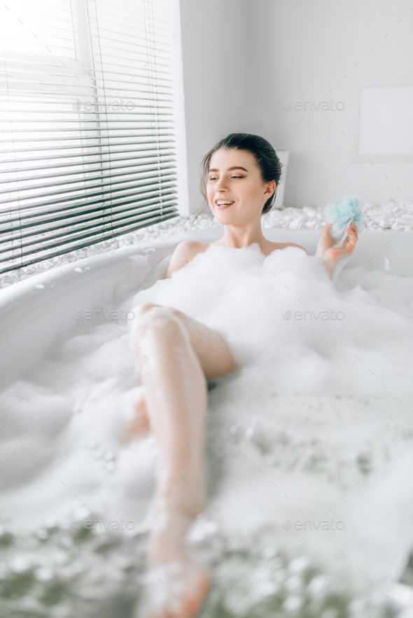 Young woman soaps the body with a sponge - Stock Photo - Images