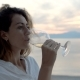 A Young Woman Sitting on the Beach and Meets a Sunset with a Glass of Wine in Her Hand - VideoHive Item for Sale
