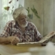 Mature Man Looking His Old Photos From Youth - VideoHive Item for Sale