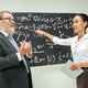 Male professor and young woman against chalkboard in classroom - PhotoDune Item for Sale