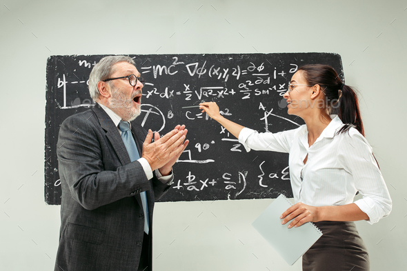 Male professor and young woman against chalkboard in classroom - Stock Photo - Images