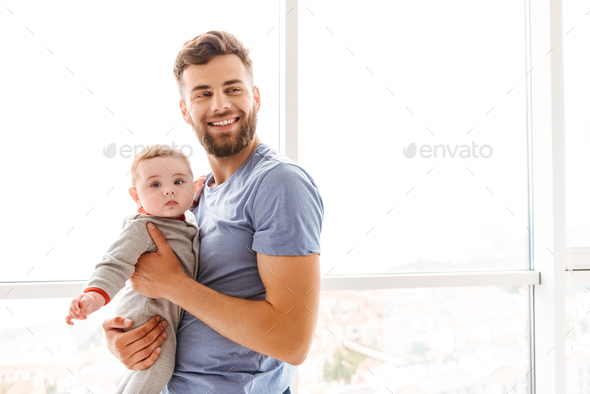 Handsome young cheerful bearded man holding his little son - Stock Photo - Images
